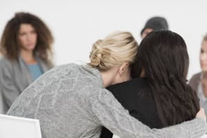woman hugs another woman getting help for addiction