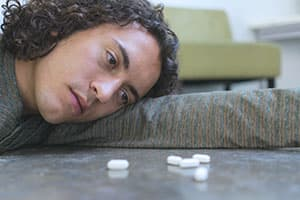 man looking at prescription pills on table