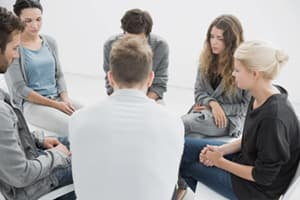 group of adults portray sitting in therapy session for recovery