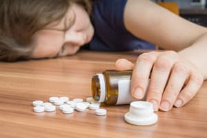 woman passed out on floor holding pill bottle overdosed on dilaudid