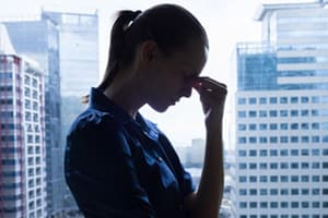woman standing in front of window with city skyline in background portraying an executive with an addiction problem