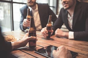 men in suits holding beers at table portraying high earning executives