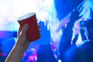 Person holding up red solo cup at a club or rave