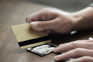 woman cutting cocaine with credit card