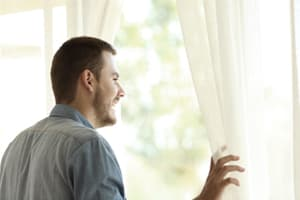 man looking out window of a luxury treatment rehab center